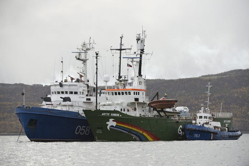 "Greenpeace ship ""Arctic Sunrise"" (C) is seen anchored outside the Arctic port city of Murmansk, on the day when members of Russian Investigation Committee conducted an inspection onboard the Greenpeace ship, in this September 28, 2013 handout provided by Greenpeace. Mandatory Credit. REUTERS/Dmitri Sharomov/Greenpeace"
