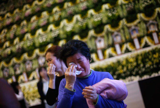 Mourners cry after paying tribute in Ansan, at a temporary group memorial altar for victims of capsized passenger ship Sewol April 23, 2014. South Korean divers swam though dark, cold waters into a sunken ferry on Wednesday, feeling for children's bodies with their hands in a maze of cabins, corridors and upturned decks as they searched for hundreds of missing. (c) REUTERS/Kim Hong-Ji