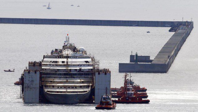 Tugboat maneuver the Costa Concordia towards its berth in the port of Genoa, July 27, 2014. REUTERS/ Stefano Rellandini