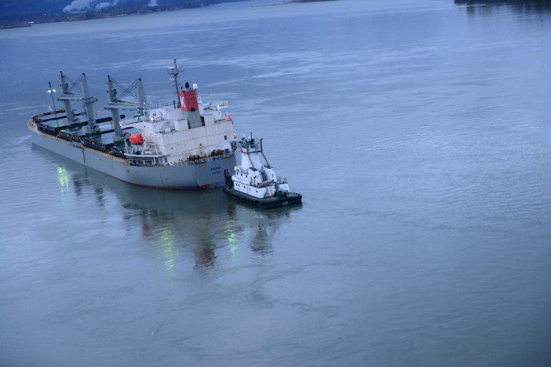 The motor vessel Sparna, a 623-foot Panamanian-flagged bulk carrier, lists to its port side after taking on water in void spaces after reportedly running aground while transiting the Columbia River near Cathlamet, Wash., March 21, 2016. The vessel is safely anchored and the Coast Guard is monitoring the situation until repairs can be made. (U.S. Coast Guard photo by Petty Officer 1st Class Levi Read)