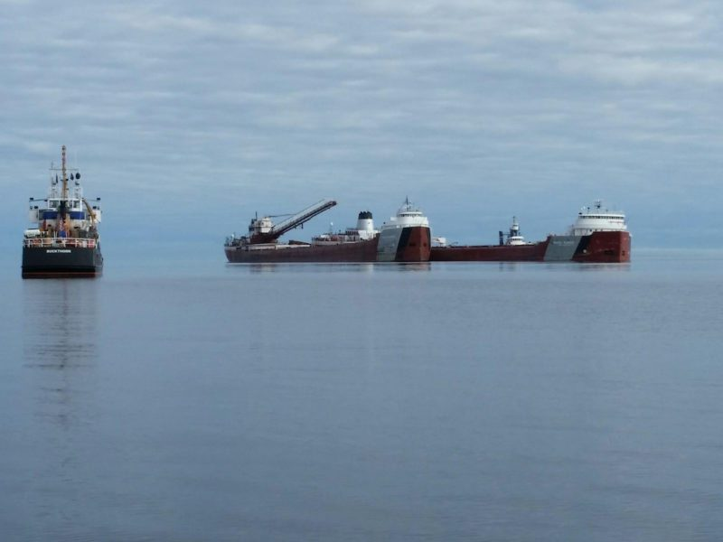 The motor vessel Phillip R. Clarke arrives on scene with the motor vessel Roger Blough that ran aground on May 27, near Gros Cap Reefs Light in Lake Superior, June 3, 2016. The Clarke is scheduled to remove some of the taconite from the Blough in order to lighten the Blough so it can be refloated, and the U.S. Coast Guard Cutter Buckthorn is on scene to enforce the 750-yard safety zone around the ships. (U.S. Coast Guard photo by Craig Gorman)